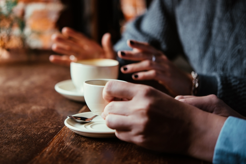Image of the hands of two people having a cup of coffee together.